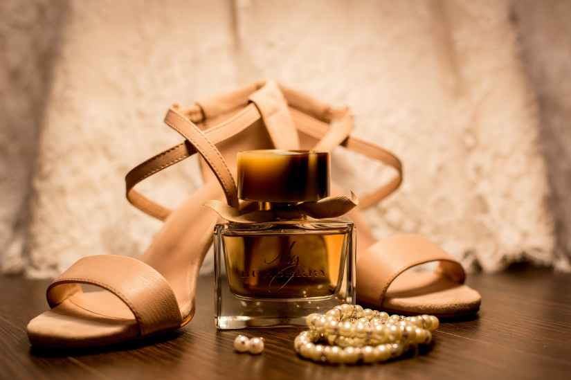 brown glass fragrance bottle beside white pearl bracelets